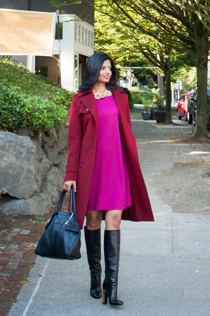 Stylish woman walking down the sidewalk holding a purse.