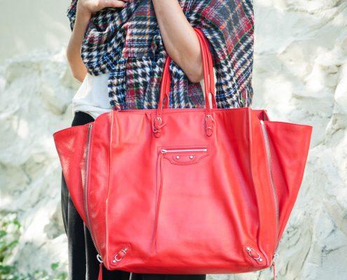 Woman holding red Balenciaga hand bag.