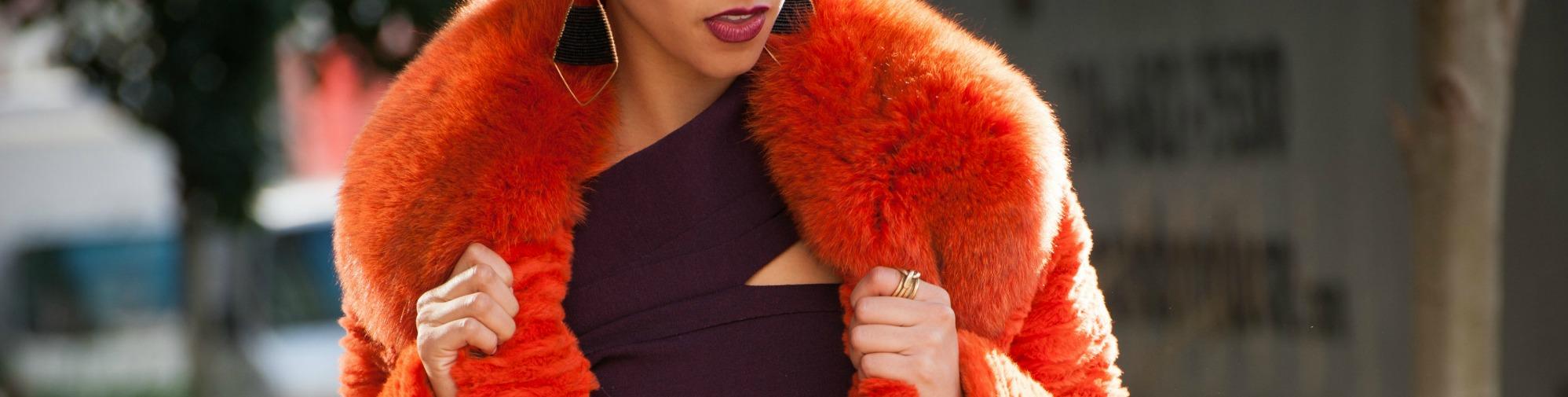 woman in purple dress and orange coat